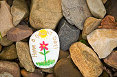 "A painted ""kindness stone"" laying in a pile of rocks that reads ""Have a nice day!"""