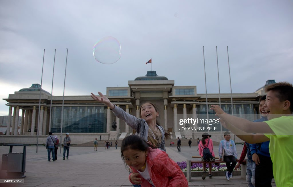 Kinds play with a bubble on the main square in front of the Mongolian Parliament House in Ulan Bator on July 1, 2016. A landslide election victory by Mongolia's opposition is a stinging rejection of the government's failed economic policies, analysts and voters said, as the country struggles to turn its vast natural resources into national wealth. / AFP / JOHANNES