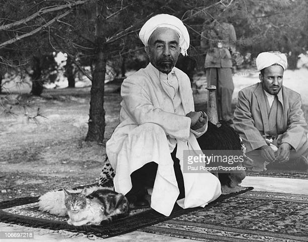King Abdullah I of Transjordan shares his rug with a pet cat in the grounds of Raghadan Palace in Amman Jordan 14th June 1948 He is resting his arm...