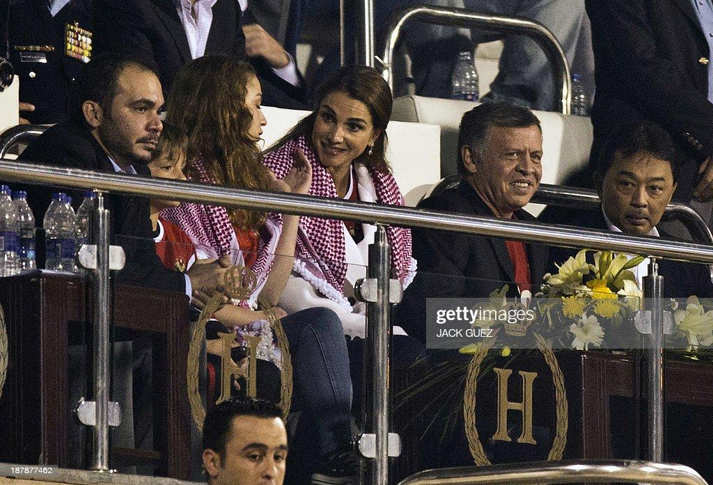 King Abdullah II of Jordan (2ndR) and Queen Rania (C) attend the FIFA 2014 World Cup qualifier (intercontinental play-off 1st leg) football match Uruguay against Jordan at the International Stadium on November 13, 2013 in the Jordanian capital, Amman. Uruguay won 5-0.