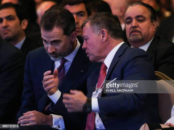 King Abdullah II of Jordan speaks with King Felipe VI of Spain during the opening session of the World Economic Forum held in the Dead Sea resort of...
