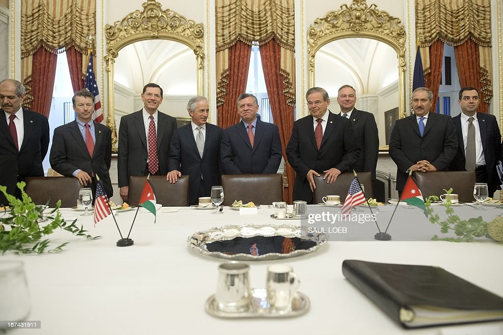 King Abdullah II of Jordan (C) stands alongside Senator Bob Corker (center L), Republican of Tennessee, Senator Robert Menendez (center R), Democrat from New Jersey, alongs with other members of the Senate Foreign Relations committee prior to meetings at the US Capitol in Washington, DC, on April 25, 2013. AFP PHOTO / Saul LOEB
