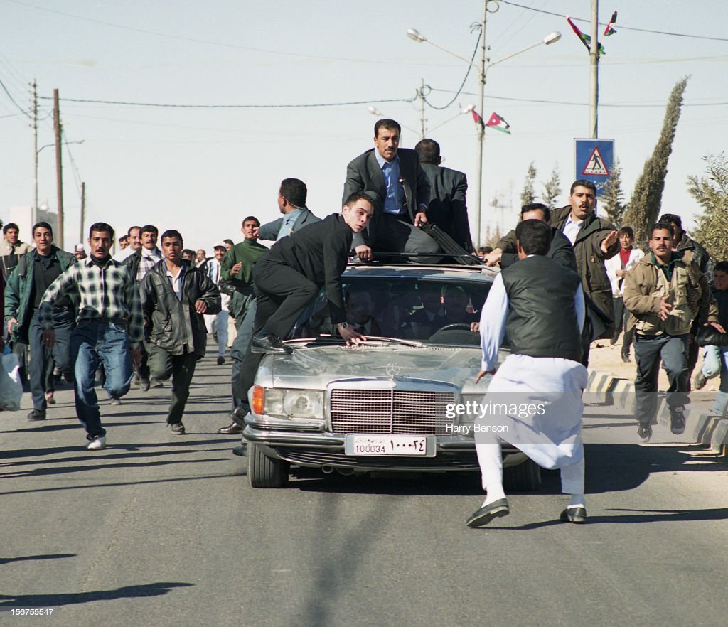 King Abdullah II of Jordan's half brother Prince Ali of Jordan is photographed on the hood of a car for Life Magazine in 2000 in Ma'an, Jordan. Prince Ali is on the hood of the King's car as a man jumps out of the crowd and tries to block the car. The King's personal bodyguard is perched on the hood. The King takes his subject's enthusiam in stride.