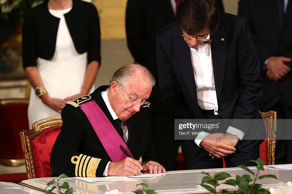 King Albert II of Belgium signs the abdication papers while being watched by Prime Minister <a gi-track='captionPersonalityLinkClicked' href=/galleries/search?phrase=Elio+Di+Rupo&family=editorial&specificpeople=743705 ng-click='$event.stopPropagation()'>Elio Di Rupo</a>a at the Abdication Ceremony Of King Albert II Of Belgium, & Inauguration Of King Philippe at the Royal Palace on July 21, 2013 in Brussels, Belgium.