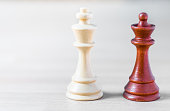 A king and a queen of different color chess pawns standing side by side on a wooden table