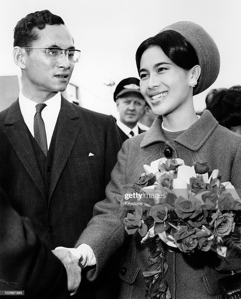 King Bhumibol Adulyadej of Thailand and Queen <a gi-track='captionPersonalityLinkClicked' href=/galleries/search?phrase=Sirikit&family=editorial&specificpeople=228360 ng-click='$event.stopPropagation()'>Sirikit</a> of Thailand, holding a bouquet of flowers, as she shakes hands with an official before boarding an aircraft at London Airport, London, Great Britain, 6 October 1966. The royal couple had been staying in Britain for eleven weeks and were returning home to Bangkok.