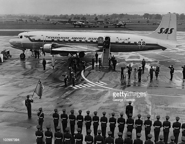 King Bhumibol Adulyadej of Thailand salutes the RAF Guard of Honour on his arrival at Gatwick Airport London at the start of a threeday state visit...