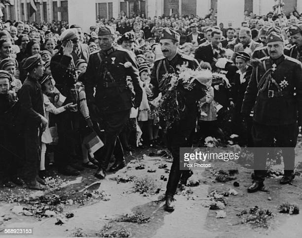 King Boris III of Bulgaria walking past crowds of people along a flower strewn path with armfuls of flowers as he celebrated the anniversary of his...