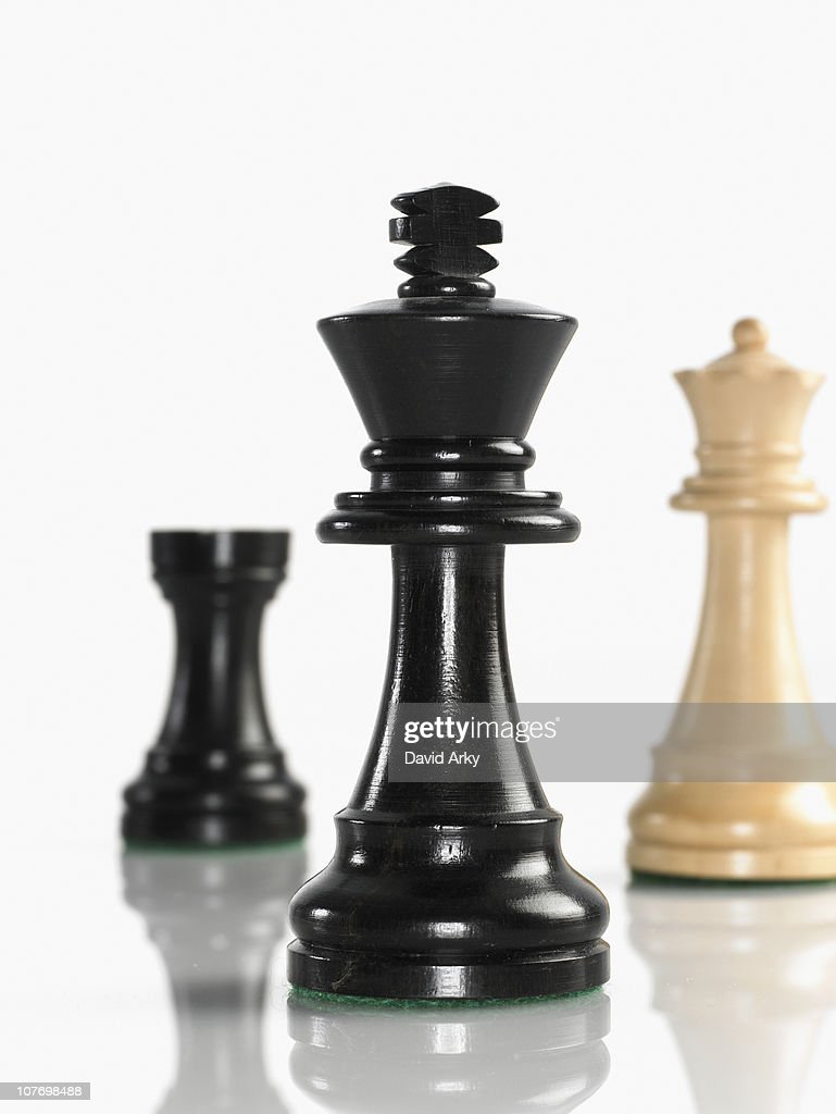 King chess piece with queen and rook in background