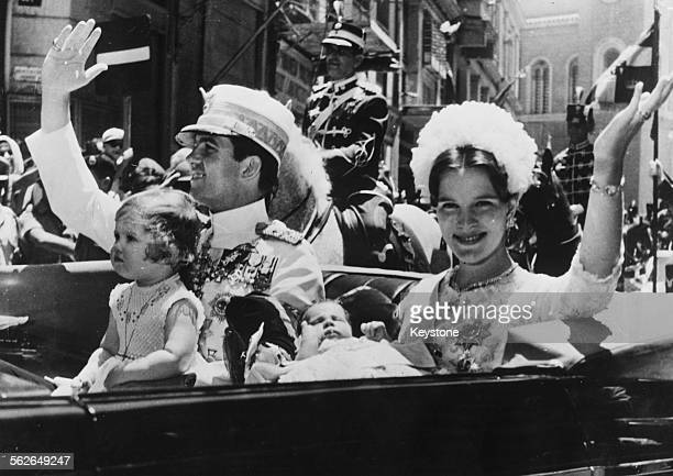 King Constantine of Greece with his wife AnneMarie and their children Princess Alexia and Crown Prince Paul waving to the crowds as they drive...