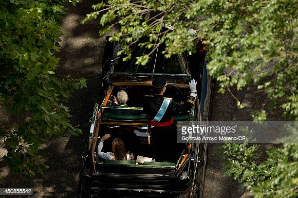 King Felipe VI of Spain and Queen Letizia of Spain wave to the crowds during the royal procession down the Gran Via on June 19 2014 in Madrid Spain...