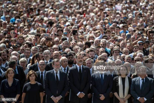 King Felipe VI of Spain and Spanish Prime Minister Mariano Rajoy join other dignitaries and residents of Barcelona in Placa de Catalunya to observe a...