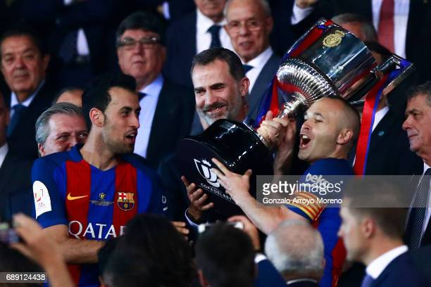 King Felipe VI of Spain gives the Cup to captain Andres Iniesta of FC Barcelona and his teammate Sergio Busquets Burgos after winning the Copa Del...