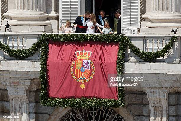 King Felipe VI of Spain kisses Queen Letizia of Spain as they greet wellwishers from the balcony of the Royal Palace during the King's official...