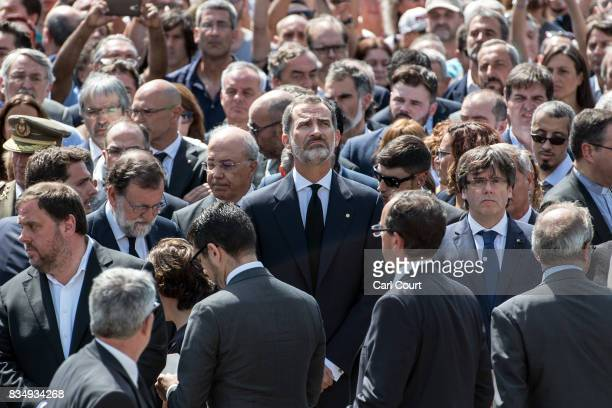 King Felipe VI of Spain looks up as he joins other dignitaries and residents of Barcelona in Placa de Catalunya to observe a one minute's silence for...