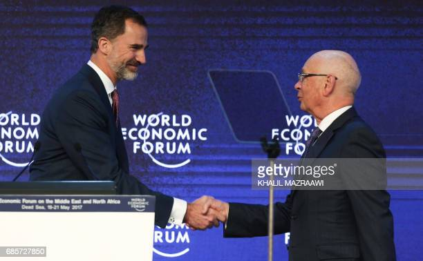 King Felipe VI of Spain shakes hands with Founder and Executive Chairperson of the World Economic Forum Klaus Schwab during the opening session of...