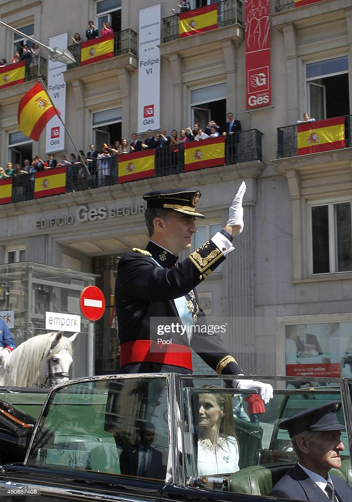King Felipe VI of Spain waves to crowds of wellwishers during his tour in an open car through the streets of central Madrid to the Royal Palace on June 19, 2014 in Madrid, Spain. The coronation of King Felipe VI is held in Madrid. His father, the former King Juan Carlos of Spain abdicated on June 2nd after a 39 year reign. The new King is joined by his wife Queen Letizia of Spain.