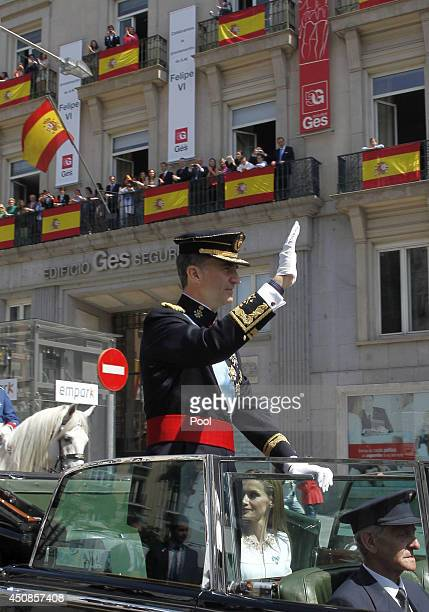 King Felipe VI of Spain waves to crowds of wellwishers during his tour in an open car through the streets of central Madrid to the Royal Palace on...