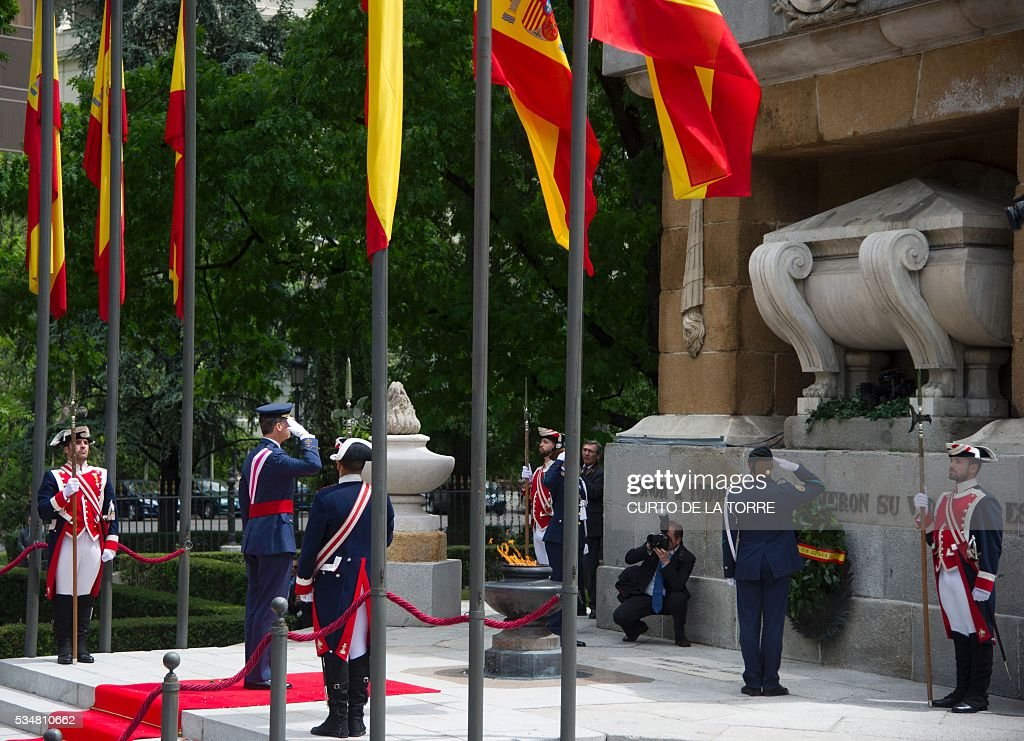 King Felipe VI salutes after laying a wreath at the foot of the war memorial on Lealtad Square during the 2016 Armed Forces Day parade in Madrid on May 27, 2016. / AFP /