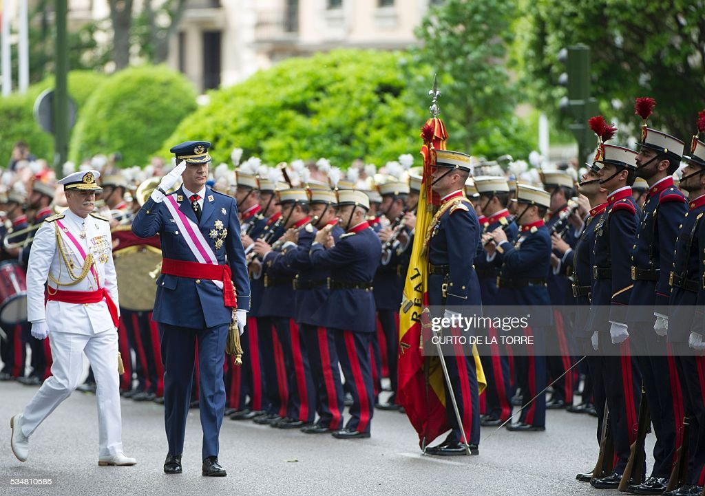 King Felipe VI salutes as he reviews troops on Lealtad Square during the 2016 Armed Forces Day parade in Madrid on May 27, 2016. / AFP /