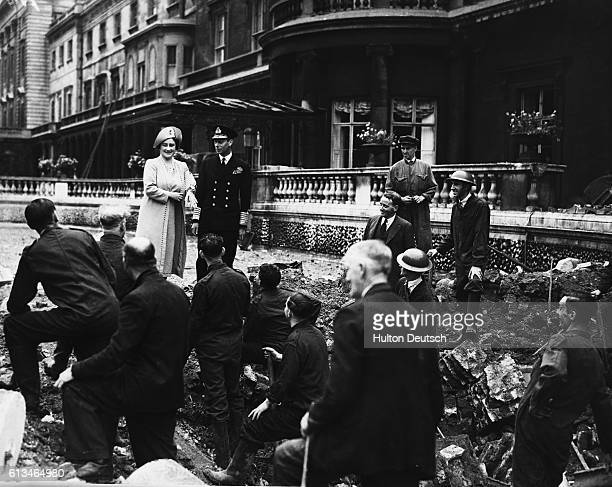 King George and the Queen Mother Elizabeth meet workers repairing bombing damage to the terraces at Buckingham Palace in September 1940