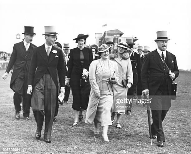 King George VI and his wife Queen Elizabeth walking with Harry Primrose 6th Earl of Roseberry at the Epsom Derby England 1938