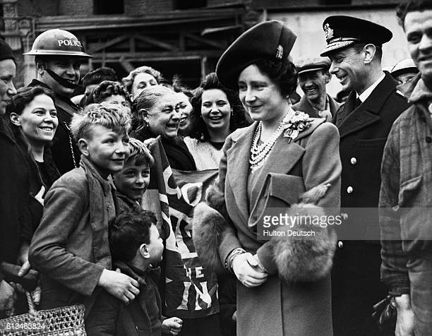King George VI and Queen Elizabeth of England tour blitzed areas of east London during World War II