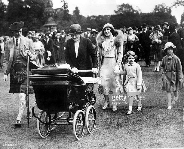 1931 King George VI and Queen Elizabeth with the young Princess Elizabeth and Princess Margaret in a pram at a garden party