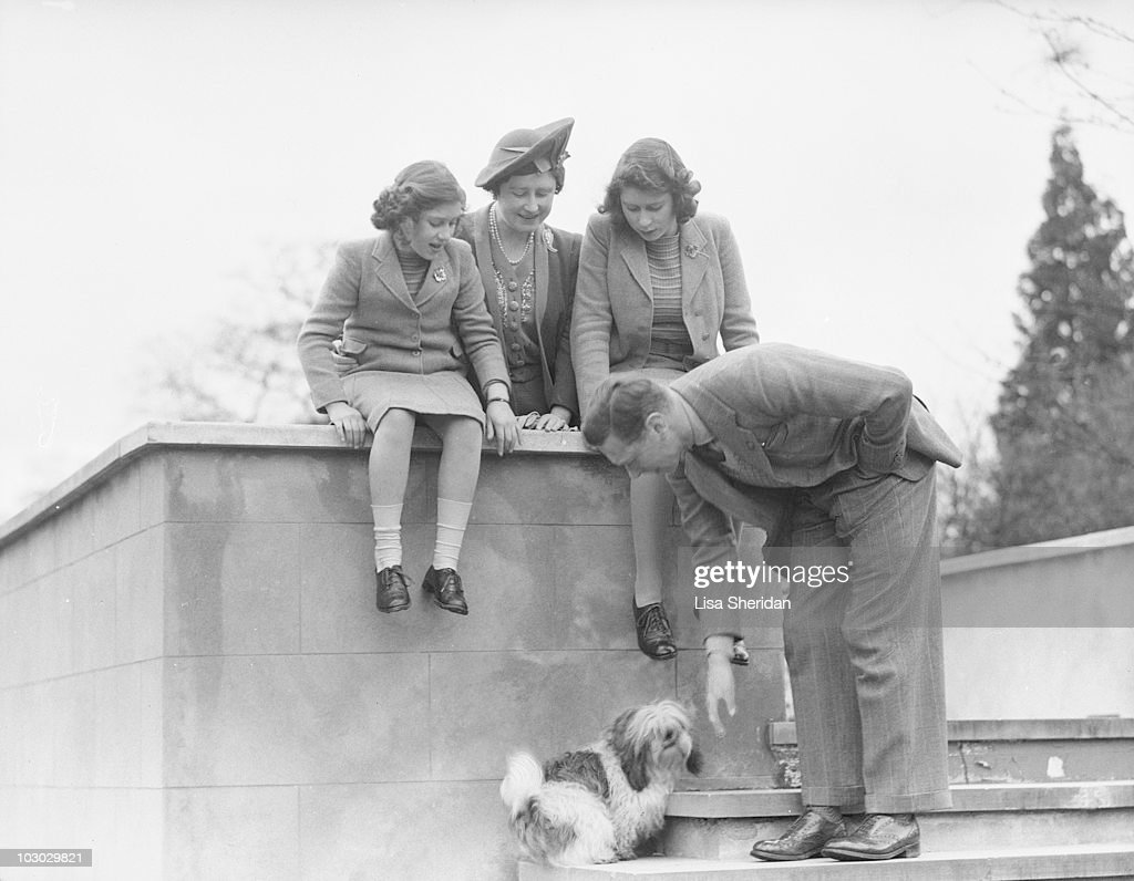 King George VI pets a dog while the Queen Elizabeth, Princess Elizabeth and Princess Margaret look on at the Royal Lodge in Windsor Castle, England on April 11, 1942.