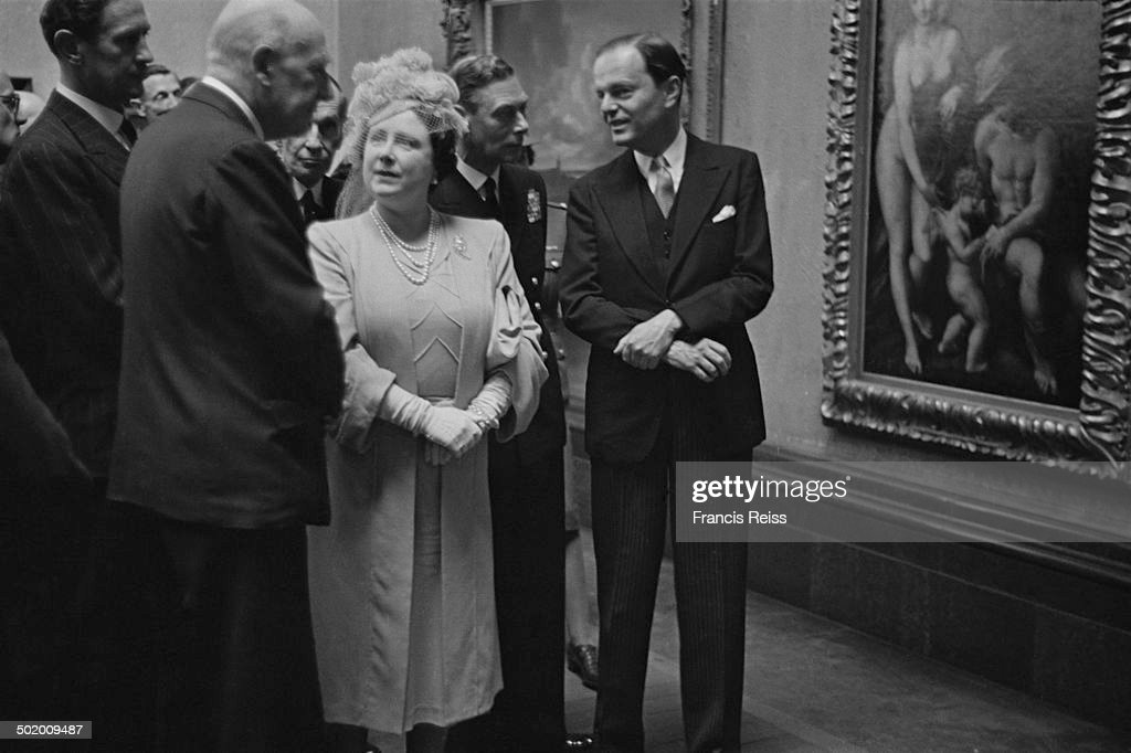 King George VI (1895 - 1952, centre) talking to Sir Kenneth Clarke (1903 - 1983, right), director of the National Gallery, while Queen Elizabeth (1900 - 2002, later Elizabeth the Queen Mother) talks to British economist John Maynard Keynes (1883 - 1946) at a National Gallery exhibition of works, which had been previously held in storage for the duration of World War II, London, June 1945. Original publication: Picture Post - 1999 - The Pictures Come Back - pub. 9th June 1945