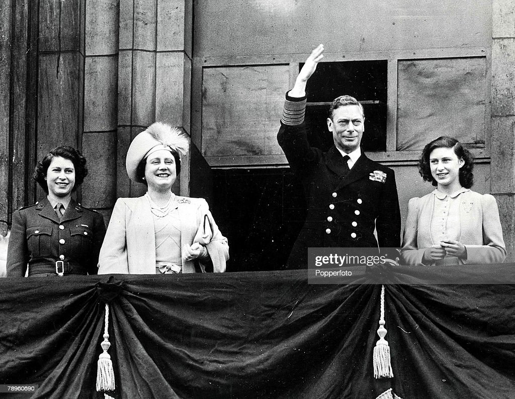 London, England, 8th May, 1945, King George VI waves from the balcony of Buckingham as he stands with Queen Elizabeth (later the Queen Mother) and their two children Princess Elizabeth (later Queen Elizabeth II) and Princess Margaret during VE Day celebrations at the end of World War Two