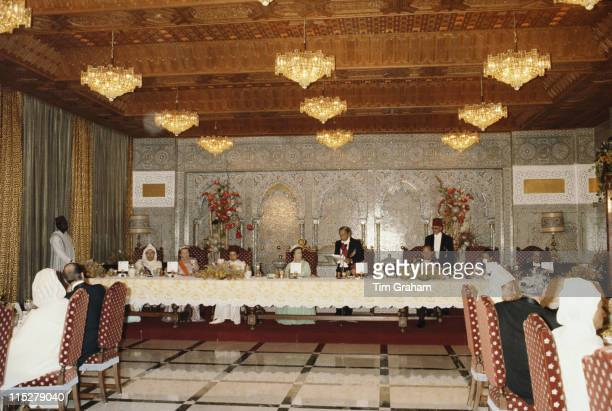 King Hassan II of Morocco makes a speech with Queen Elizabeth II and Prince Philip sitting either side of him at a state banquet at the royal palace...