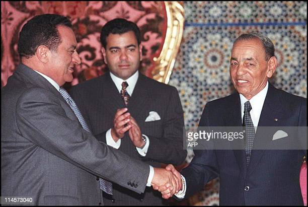 King Hassan II of Morocco shakes hands with Egyptian President Hosni Mubarak 14 May at the royal palace in Rabat as Moroccan Prince Moulay Rachid...