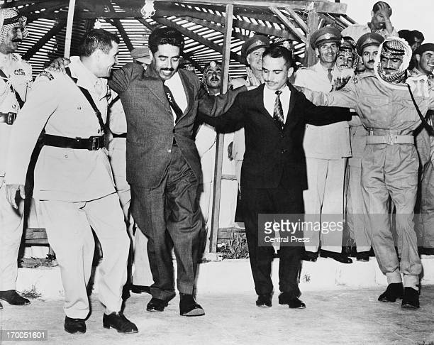 King Hussein of Jordan dancing arminarm at a ceremonial dance during a military display to begin the Army Day and independance celebrations Amman...