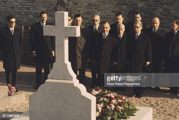 King Hussein of Jordan pictured in centre pays his respects as he stands with officials and diplomats in front of the grave of President Charles de...