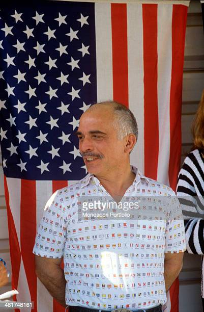 King Hussein of Jordan portrayed as he smiles in a relaxed pose his hands behind his back sporting a fancy white polo shirt with printed miniatures...