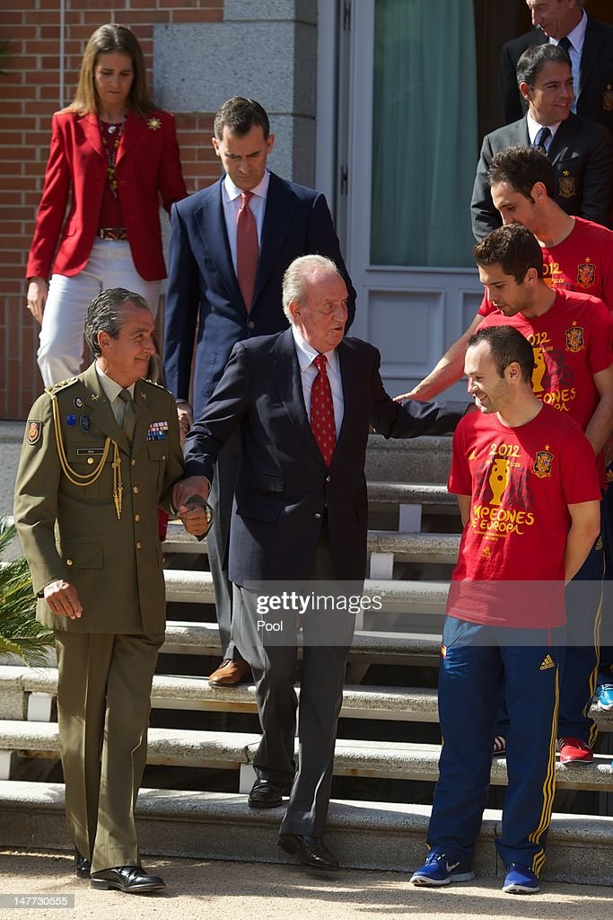 King Juan Carlos I of Spain (C) is helped down some steps in front of Prince Felipe of Spain and Princess Elena of Spain as he speaks with Andres Iniesta (front), <a gi-track='captionPersonalityLinkClicked' href=/galleries/search?phrase=Jordi+Alba&family=editorial&specificpeople=5437949 ng-click='$event.stopPropagation()'>Jordi Alba</a> (C) and Juanfran of Spain as he receives members of Spain's victorious UEFA EURO 2012 football squad at Zarzuela Palace on July 2, 2012 in Madrid, Spain.