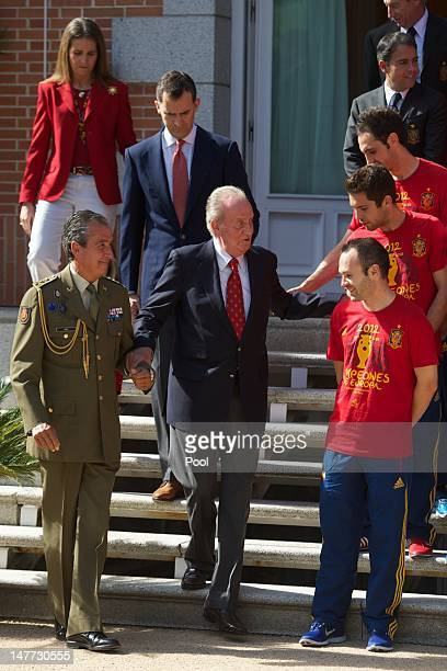 King Juan Carlos I of Spain is helped down some steps in front of Prince Felipe of Spain and Princess Elena of Spain as he speaks with Andres Iniesta...
