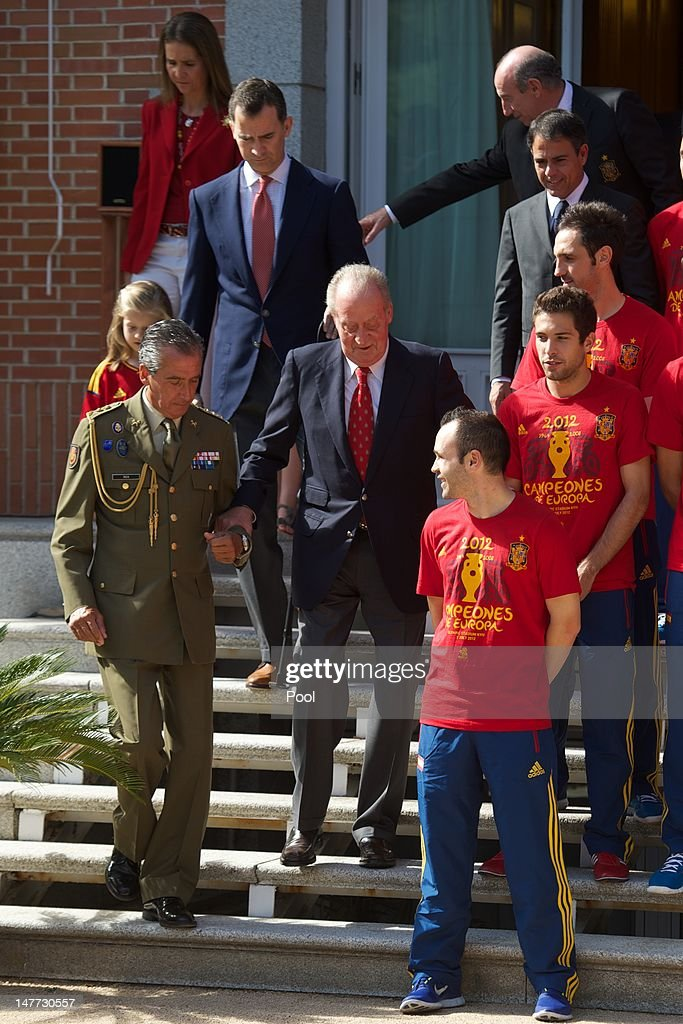 King Juan Carlos I of Spain (C) is helped down some steps in front of Prince Felipe of Spain and Princess Elena of Spain as he speaks with Andres Iniesta (front), Jordi Alba (C) and Juanfran of Spain as he receives members of Spain's victorious UEFA EURO 2012 football squad at Zarzuela Palace on July 2, 2012 in Madrid, Spain.