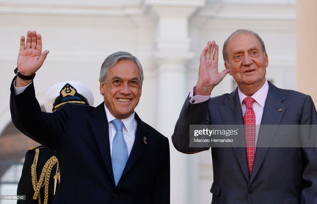 King Juan Carlos of Spain (R) and the President of Chile Sebastián Piñera (L) greet people during the visit to the Presidential Palace on June 5, 2012 in Santiago, Chile.