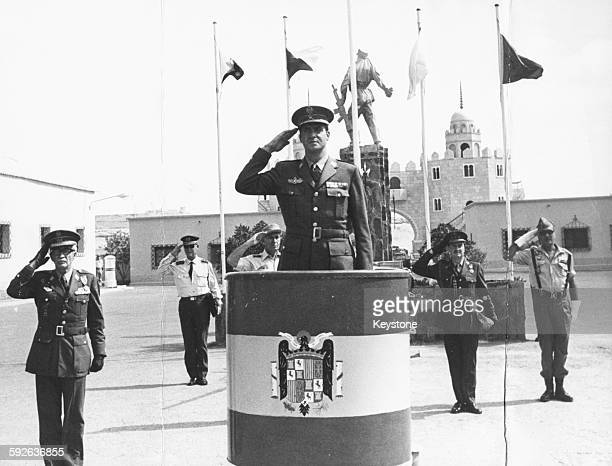 King Juan Carlos of Spain saluting on a podium during a review of Spanish troops in El Aaiun November 5th 1975