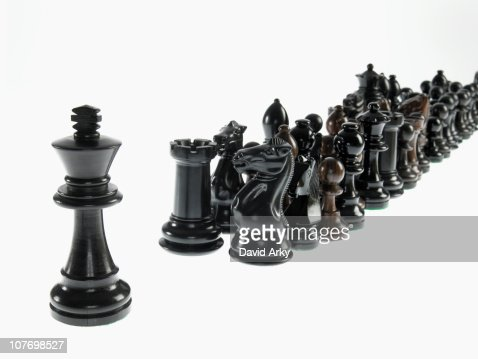 King leading black chess pieces