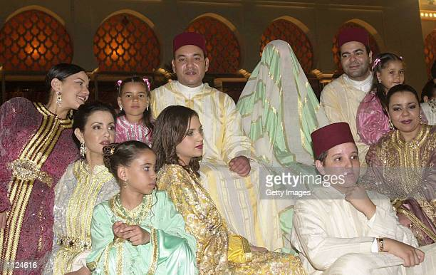 King Mohammed VI sits with his veiled bride Salma Bennani and his brother Prince Moulay Rachid while surrounded by members of the Royal family July...