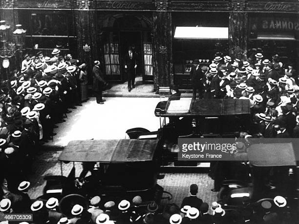 King of Spain Alfonso XIII walks out of the Cartier store in the Rue de la Paix surrounded by a crowd of spectators in 1922 in Paris France