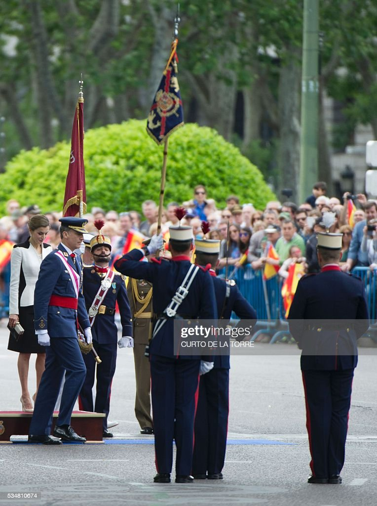King of Spain Felipe VI (2L) and Queen of Spain Letizia (L) walk on Lealtad Square during the 2016 Armed Forces Day parade in Madrid on May 27, 2016. / AFP /