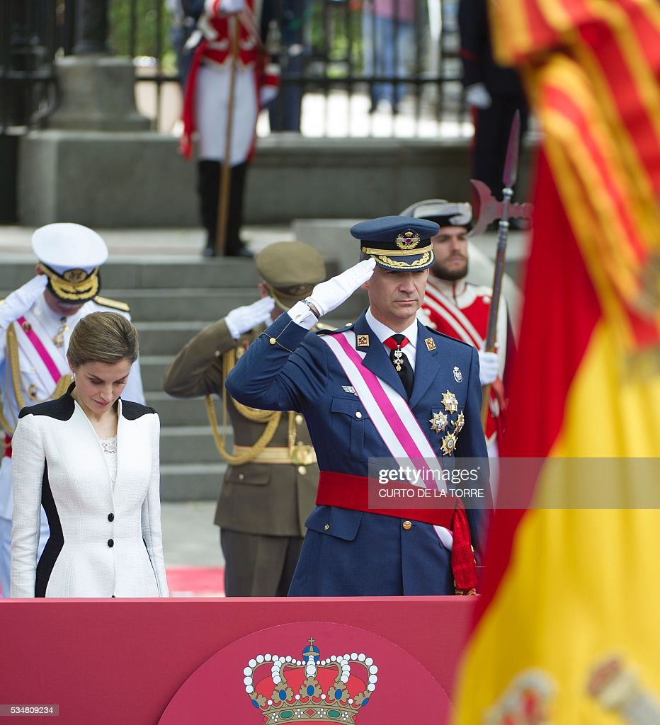 King of Spain Felipe VI (R) salutes troops beside Queen of Spain Letizia during the 2016 Armed Forces Day parade in Madrid on may 27, 2016. / AFP / CURTO