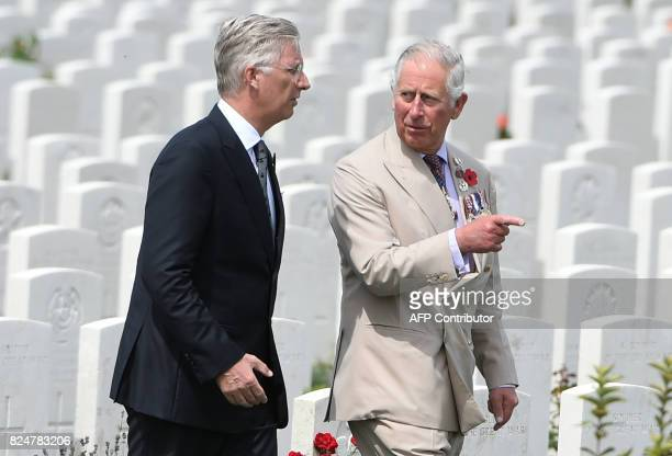 King Philippe of Belgium and Britain's Prince Charles speak with each other as they walk past headstones of soldiers who fell in World War One at The...