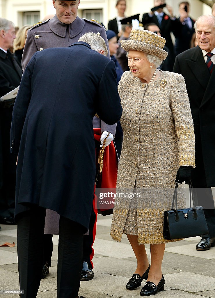 King Philippe of Belgium kisses the hand of Queen Elizabeth II as they attend the opening of the Flanders' Fields Memorial Garden on November 6, 2014 in London, England.
