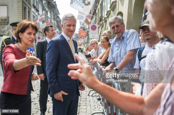 King Philippe of Belgium shakes hands with spectators next to Swiss President Doris Leuthard at the start of his official visit to Switzerland on...