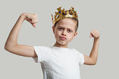 The little boy with a royal crown shows muscles.